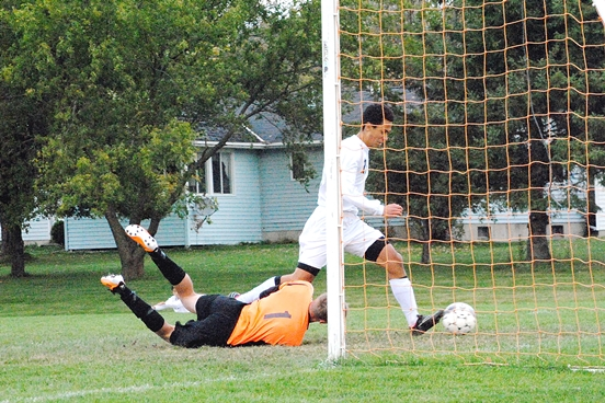 Marshfield's Chris Pahl beats Stevens Point goalkeeper Ryan Weber to the ball to score a goal during the first half of Tuesday's Wisconsin Valley Conference boys soccer game at Griese Park. (Photo by Paul Lecker/MarshfieldAreaSports.com)