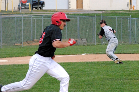 Marshfield third baseman Sam Klein makes a throw to home as Stevens Point's Brady Erickson runs to first baseman during the first inning of Tuesday's game at Hackman Field. (Photo by Paul Lecker/MarshfieldAreaSports.com)