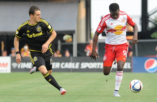 Columbus Crew SC midfielder Ethan Finlay, left, a 2008 Marshfield High School graduate, chases down the New York Red Bulls' Anatole Abang during a recent MLS game. Finlay leads the MLS in assists with 11 through 21 games. (Photo courtesy of Sean Duffy/Columbus Crew SC)