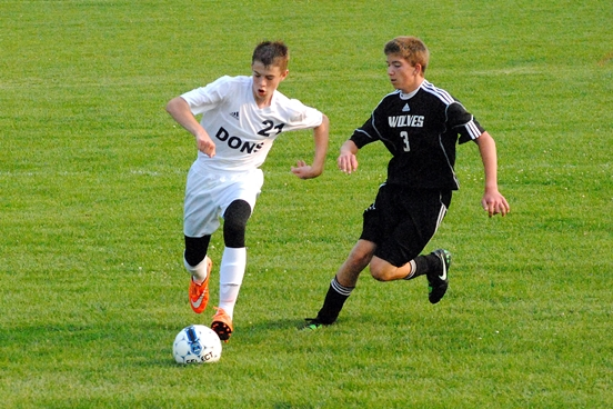 Columbus Catholic's Nick Malovrh (left) sprints past Wisconsin Valley Lutheran's Wyatt Anklam during Monday's soccer game at Griese Park in Marshfield. The Dons won 5-0. (Photo by Paul Lecker/MarshfieldAreaSports.com)